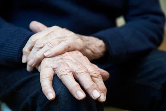 Une personne atteinte par la maladie de Parkinson tente de limiter les tremblements de sa main