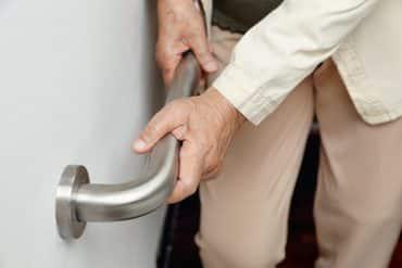 Une personne âgée s'accroche à une barre d'escalier pour éviter la chute
