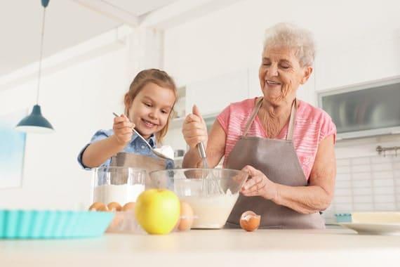 Une personne âgée et sa petite fille préparent une recette lors d'une session de cuisine thérapie