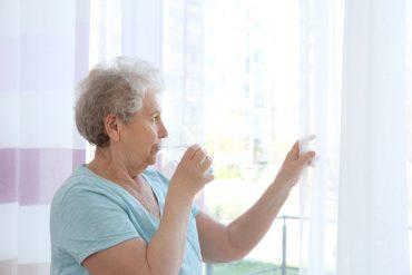 Une personne âgée se protège de la canicule en restant à l'intérieur et en buvant de l'eau