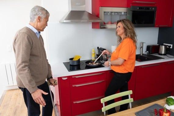 Une aide à domicile prépare le repas d'une personne en situation de handicap qui utilise une béquille