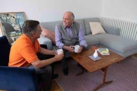 Une aide à domicile prend le thé avec un bénéficiaire en perte d'autonomie