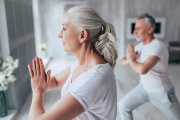Photographie d'un couple de seniors habillés en vétements de sport et réalisant une séance de yoga à domicile