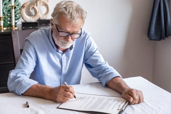 Un senior en chemise entrain de faire un testament olographe