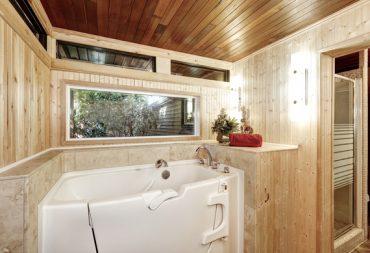 Photo d'une baignoire avec porte installée dans une salle de bain en bois
