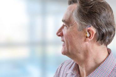 Un senior utilise un appareil auditif et peut réentendre les conversations autour de lui